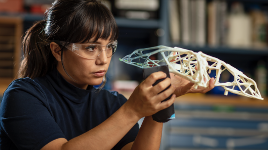 Woman wearing protective goggles looking at a miniature structure in a her hand