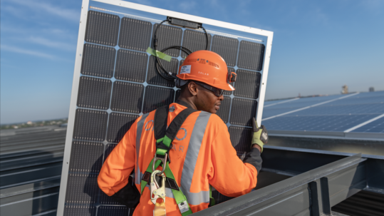 Construction worker in protective clothing carrying a solar panel