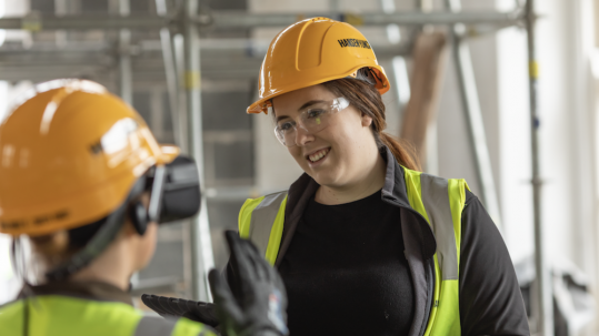Two women in protective clothing on a construction site
