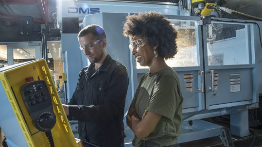 Man in overalls in a factory with a woman overseeing both wearing protective goggles